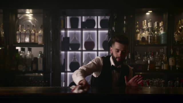 The bartender is wiping the bar with a towel. 4K