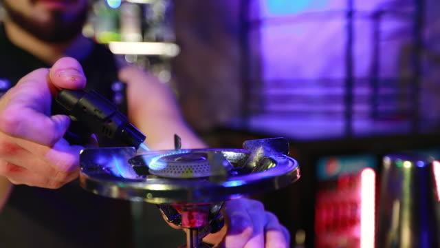 バーテンダーは、夜のバーでガスのリングを点灯します。 - 異国情緒点の映像素材/bロール