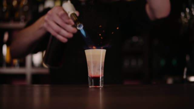 the bartender makes a cocktail of fire. hiroshima cocktail. the barman ignites the lighter on the bar - ice on fire video stock e b–roll