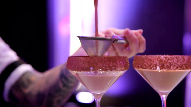 the bartender pours the cocktail into the glass video