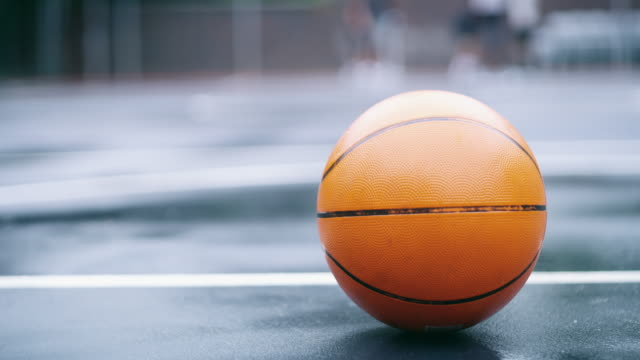 The battle is about to begin 4k video footage of a basketball on a basketball court with players in the background focus on foreground stock videos & royalty-free footage