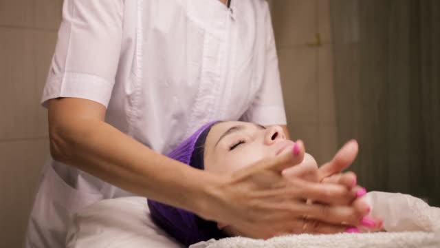 die kosmetikerin massiert das gesicht im schönheitssalon - patientin stock-videos und b-roll-filmmaterial