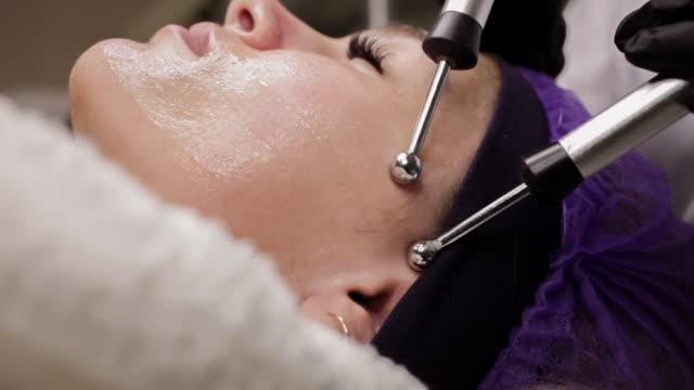 die kosmetikerin führt das mikrostromverfahren im schönheitssalon durch. - patientin stock-videos und b-roll-filmmaterial