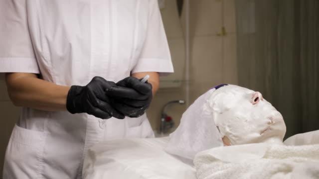 die kosmetikerin führt den eingriff der mesotherapie durch - patientin stock-videos und b-roll-filmmaterial