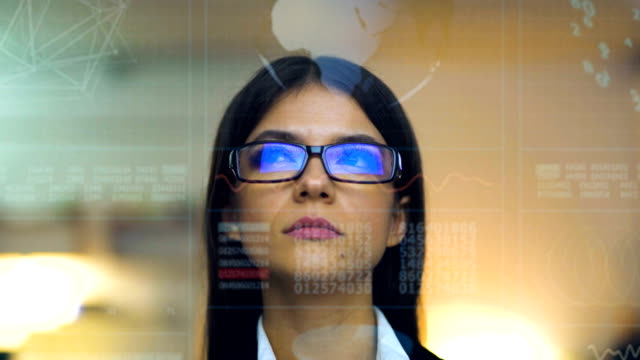 the beautiful businesswoman in glasses on the hologram background - glass world video stock e b–roll