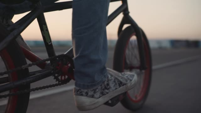 The bicyclist rides on his bmx outdoors at sunset. Slow motion close-up