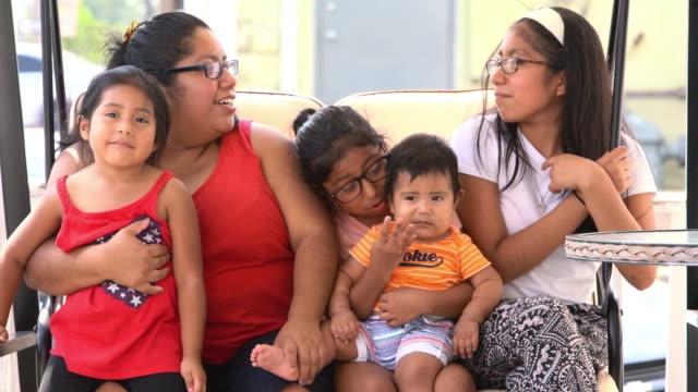 The big happy Latino Mexican-American family resting at the porch of his house - vídeo