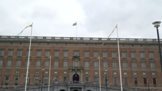 The big red palace building in the streets of Stockholm Sweden The big red palace building in the streets of Stockholm Sweden with the flag poles outside the green lawn royalty stock videos & royalty-free footage