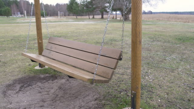 The big wooden swing on the playground in Varska Estonia The big wooden swing on the playground in Varska Estonia with the chains on the side outdoor play equipment stock videos & royalty-free footage