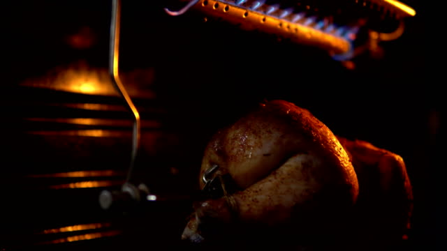 The bird on a spit turns and is fried under a gas burner in the oven. video