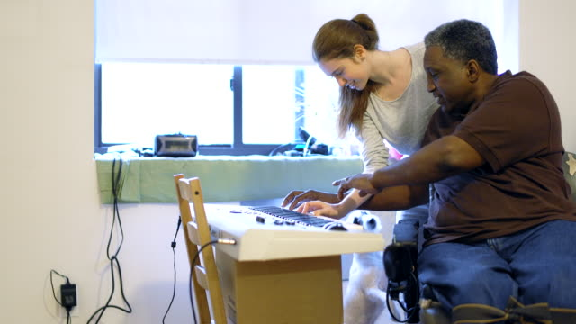 The Black disabled man teaching the attractive White teenager girl to play piano keyboard video