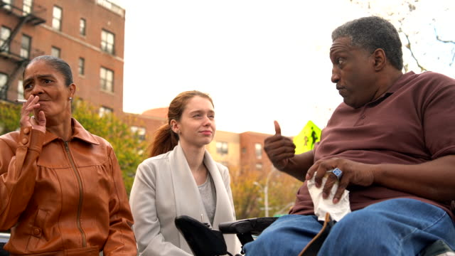 The Black disabled man, veteran in wheelchair, telling the story to the White teenager girl. video