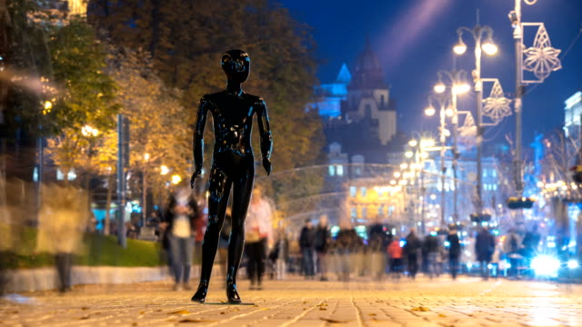 The black mannequin standing in a people crowd in the evening street. time lapse