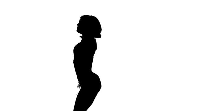 vidéos et rushes de la silhouette noire d'une jeune fille danse sur un fond blanc - twerk