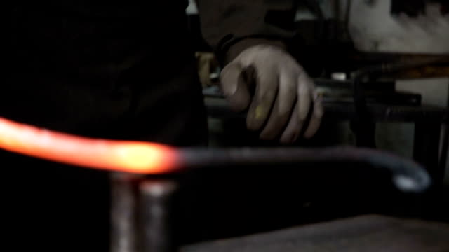 the blacksmith makes metal candle holder with rose and horseshoe. video