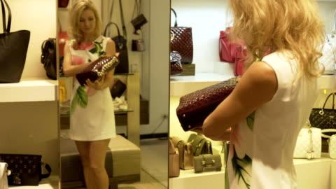stockvideo's en b-roll-footage met de blonde kiest een handtas staande door de spiegel in de kledingwinkel. - alleen volwassenen