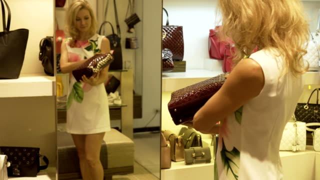 blondinen väljer en handväska stående genom spegeln i arkivet kläder. - endast vuxna bildbanksvideor och videomaterial från bakom kulisserna