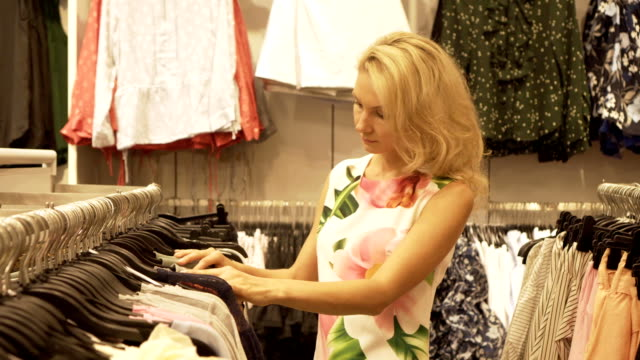 the blonde girl chooses clothes hanging on the hangers in the clothing shop. - modella negozio video stock e b–roll