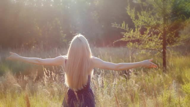 la ragazza bionda rase la sua disposizione al sole. concetto di libertà. - abbigliamento da neonato video stock e b–roll