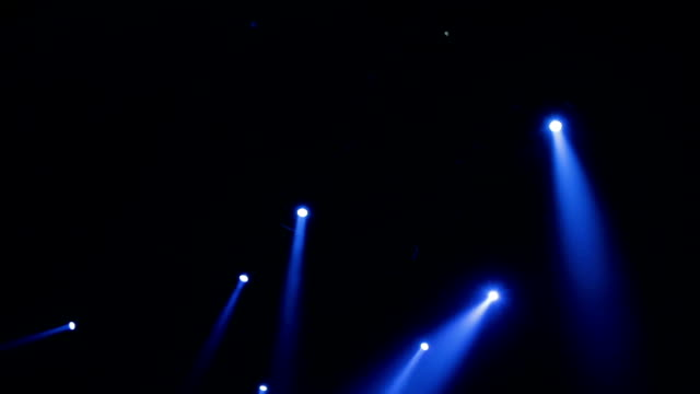 The blue light from the spotlights through the smoke in the theatre during the performance. Lighting equipment video