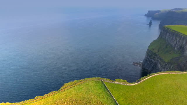 The blue sea and the green field in Cliffs of Moher in Ireland video