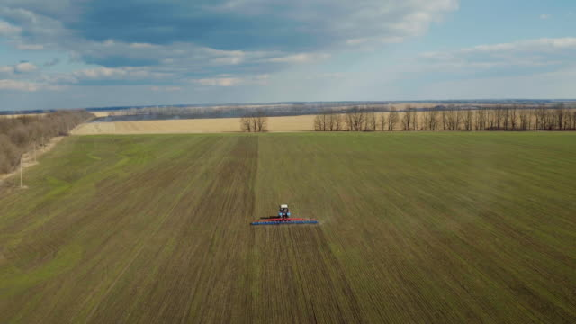 The blue sky and the green field below in the spring day. The tractor treats the soil below, picturesque aerial video video