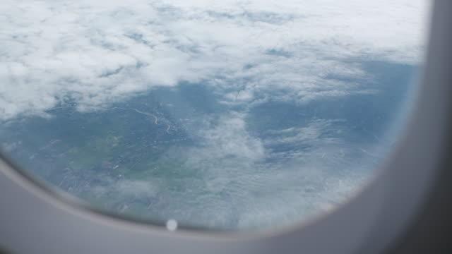 vídeos de stock, filmes e b-roll de o azul do céu em dia nublado, através de uma janela de avião - paisagem urbana