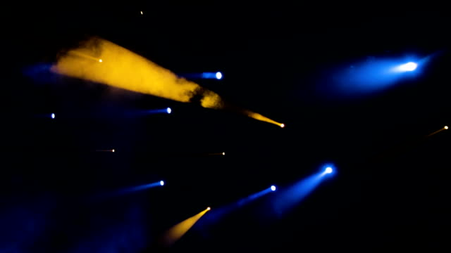 The blue-yellow light from the spotlights through the smoke in the theatre during the performance. Lighting equipment video