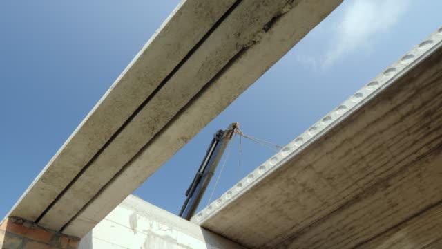 boomen av kranen installerar en tung armerad betong panel för golvet. byggandet av hus koncept - construction workwear floor bildbanksvideor och videomaterial från bakom kulisserna