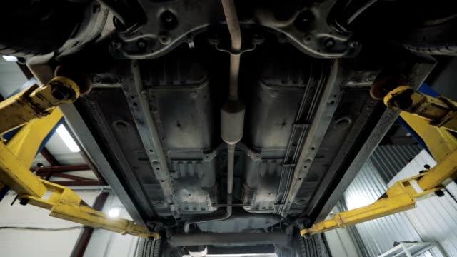 botten av bilen. garage-tjänst. bil diagnostiska - verkstad bildbanksvideor och videomaterial från bakom kulisserna