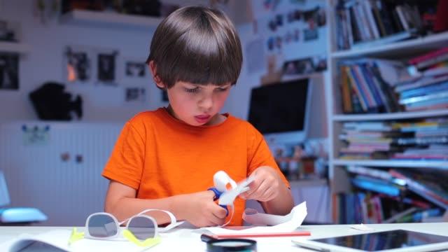 餐桌上的男孩剪出一張紙 - 手工藝 個影片檔及 b 捲影像