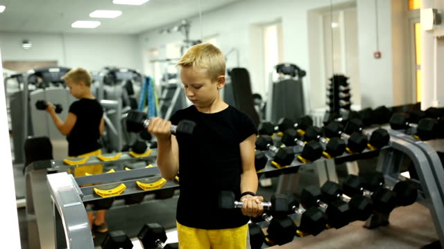 The boy does heavy dumbbell exercises for the biceps.