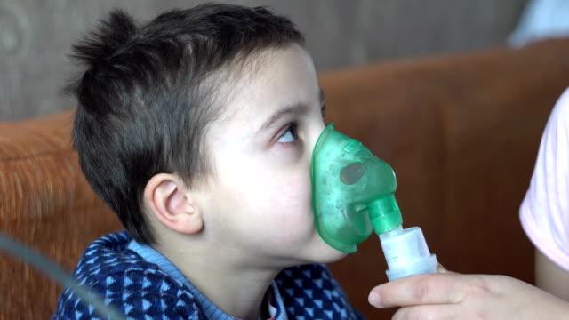 the boy does inhalation in the room - flu shot стоковые видео и кадры b-roll