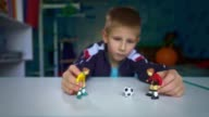 istock The boy dreams of playing soccer with friends. Sad boy playing figures of football players. 1228640857