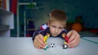 istock The boy dreams of playing soccer with friends. Sad boy playing figures of football players. 1255101416