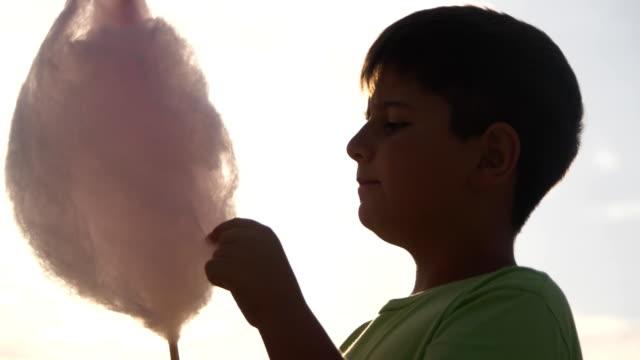 el chico en los rayos de la puesta del sol tiene algodón dulce - vídeo