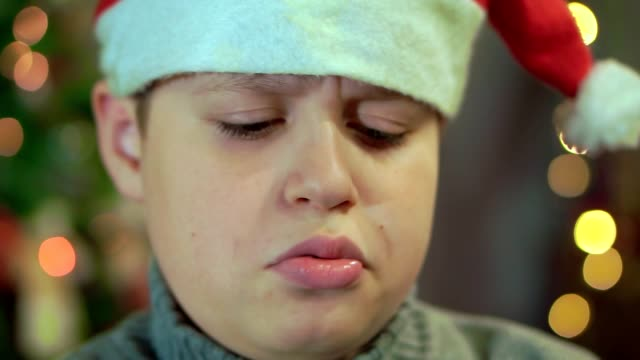 the boy in the sweater and the hat of santa claus is upset and offended. he has no gift. extra close-up, against the background of christmas lights - rabbia emozione negativa video stock e b–roll