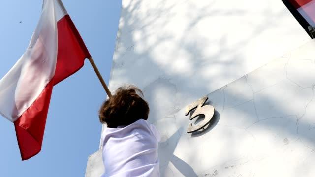 der junge hängt eine fahne. polnischer nationalfeiertag des dritten mai, verfassungstag - polnische kultur stock-videos und b-roll-filmmaterial