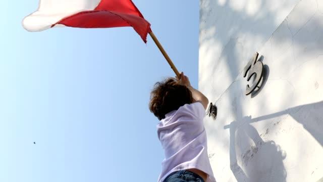 El chico está colgando una bandera. Día nacional polaco del tercer de mayo, día de la Constitución - vídeo