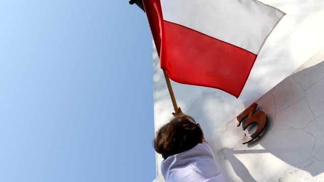 vídeos y material grabado en eventos de stock de el chico está colgando una bandera. día nacional polaco del tercer de mayo, día de la constitución - día del trabajo