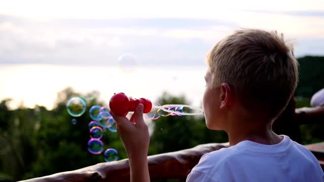 the boy is making soap bubbles. panoramic view. closeup. - solo bambini maschi video stock e b–roll