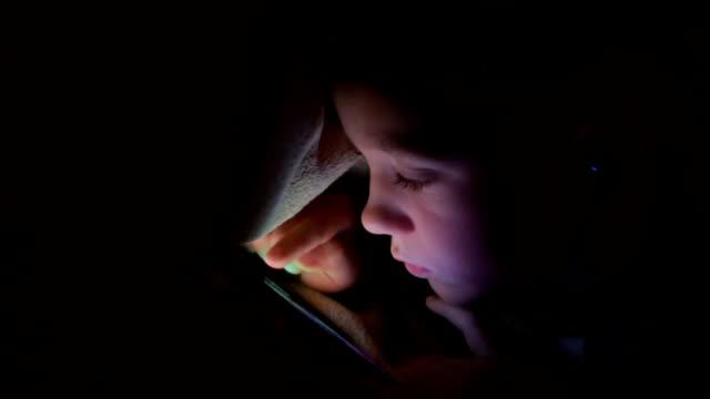 少年が毛布の下ではなく、携帯電話を再生します。 - スマホ ベッド点の映像素材/bロール