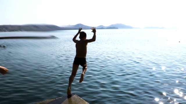 The boy jumps into the water from the pier video