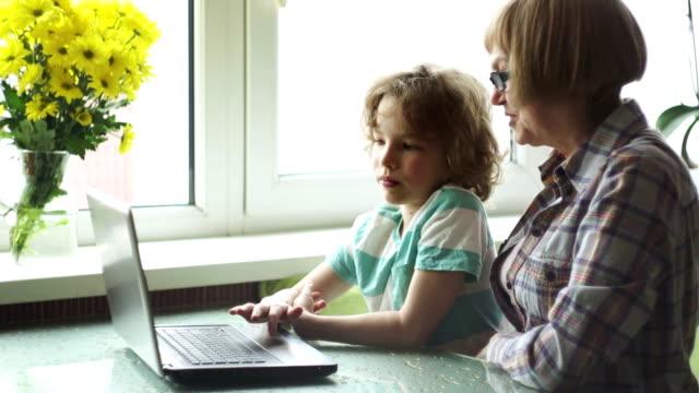 vídeos y material grabado en eventos de stock de el niño de la edad escolar más joven ayuda a la anciana a dominar la computadora. - árboles genealógicos
