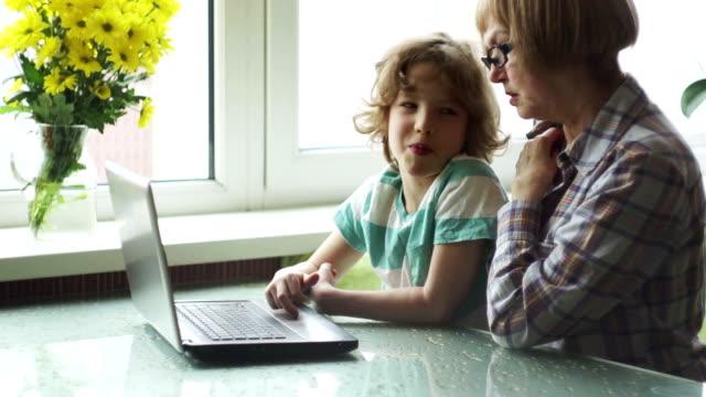 若い学年の男の子は、高齢の女性がコンピュータを習得するのに役立ちます。 - 家系図点の映像素材/bロール