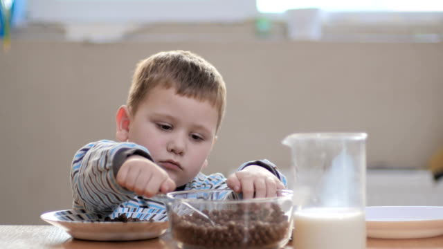 The boy puts the flakes in his plate and thumb up video