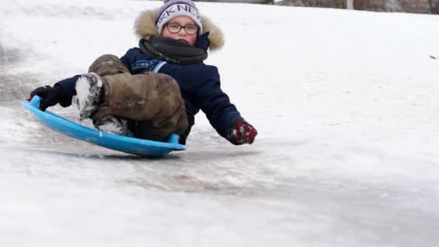pojken rider en släde på vintern från en kulle - diabild bildbanksvideor och videomaterial från bakom kulisserna