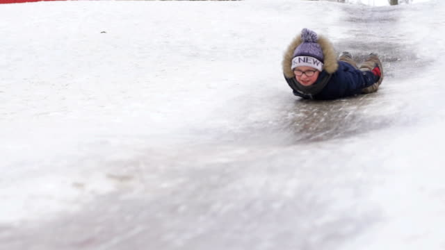 the boy rolls on an icy hill lying - scivolo video stock e b–roll