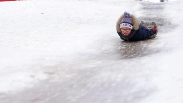 the boy rolls on an icy hill lying - slitta video stock e b–roll