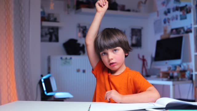 the boy sits at a table in school, raises his hand to the top a boy in an orange T-shirt, sits at a table at school, raises his hand to the top, ready to answer a survey one boy only stock videos & royalty-free footage